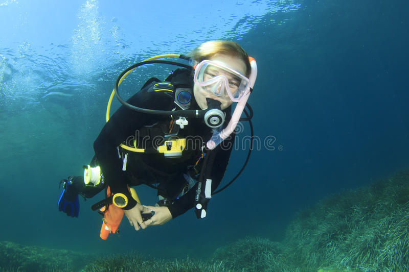Young woman scuba diving royalty free stock image