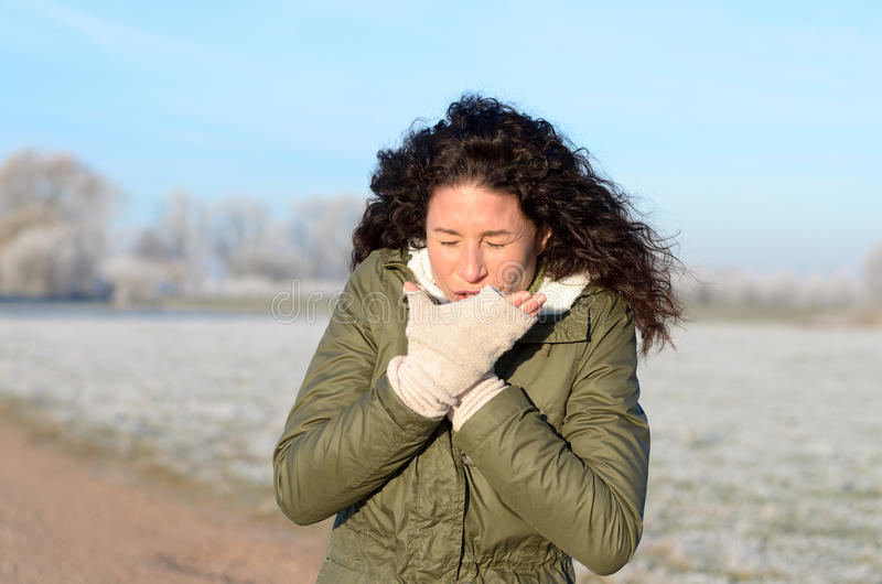 Young woman with a seasonal cold and flu. Coughing into her gloved hand as she stands on a rural road in a cold frosted winter landscape in sunshine, close up stock image