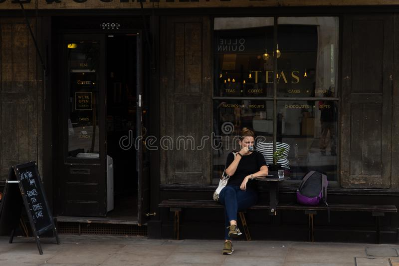 Young woman seated in front of a cafe bar stock photos