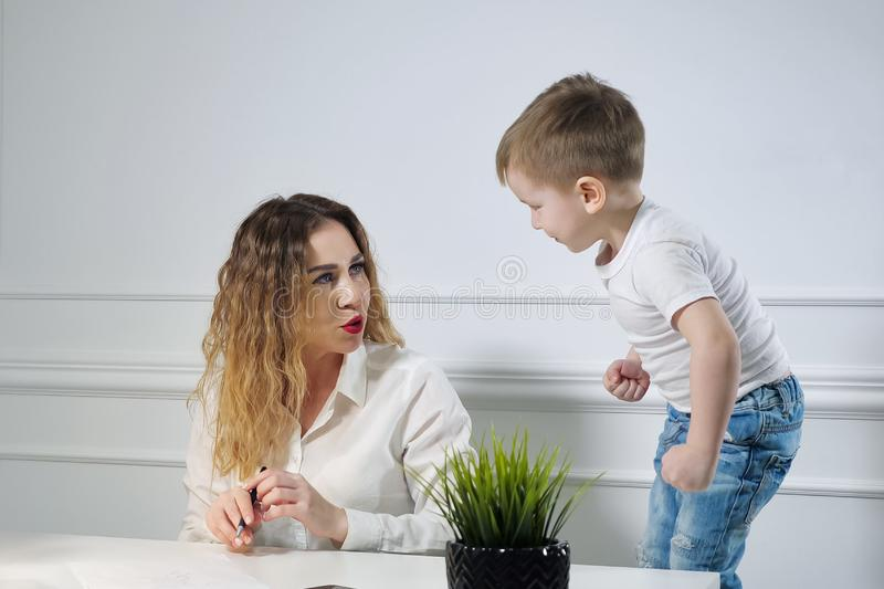 Young woman secretary with her little son in the workplace in office. Working mother. stock photo