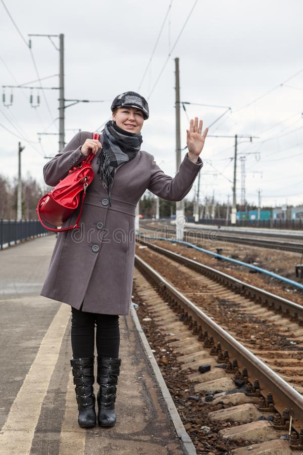 Young woman sees off her friend and waving on platform of railroad station stock photography