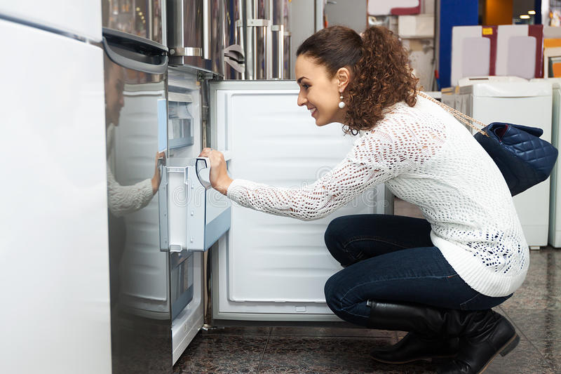 Young woman selecting domestic refrigerator. Cheerful young woman selecting domestic refrigerator in supermarket stock photos