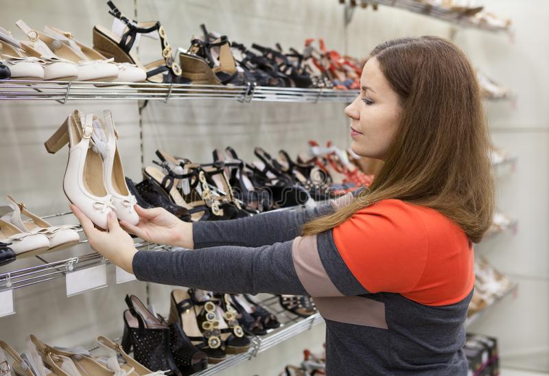 Young woman selecting new shoes in store, holding hand barefoot slippers royalty free stock images