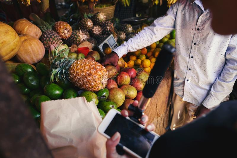 Young woman selects fruit on local African market royalty free stock photography