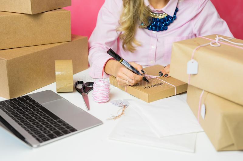 Young woman selling products online and packaging goods for shipping. Woman selling products online and packaging goods for shipping royalty free stock image