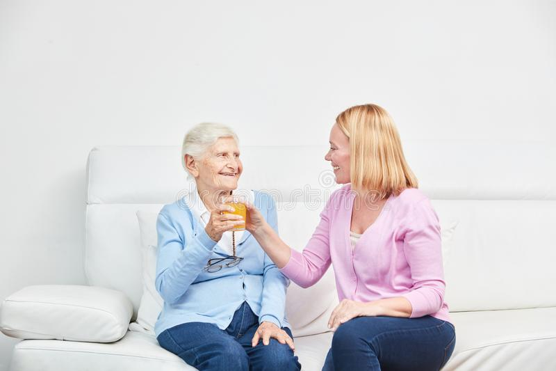 Young woman and senior woman drink juice together stock photos