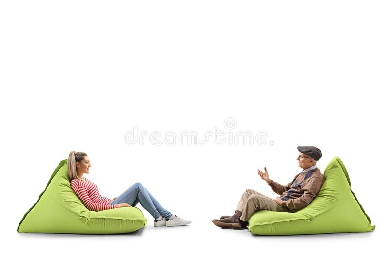Young woman and a senior man sitting on bean bags and having a conversation royalty free stock photos