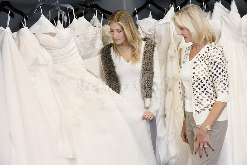Young woman with senior mother selecting wedding dress in bridal store royalty free stock photo