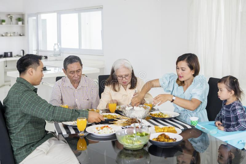 Young woman serving foods for her big family stock photo