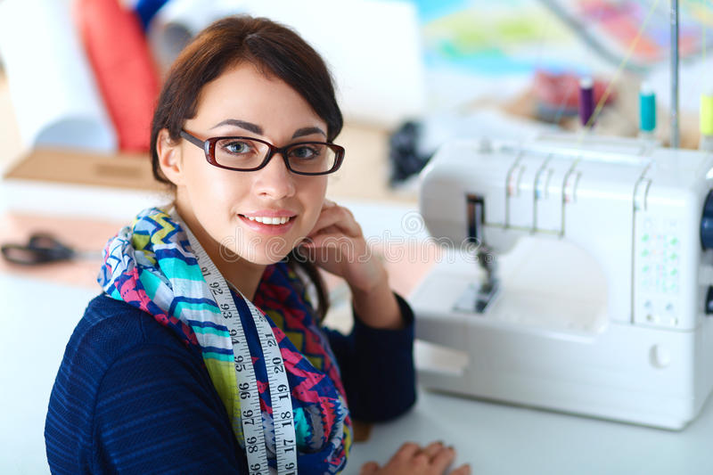 Young woman sewing while sitting at her working place royalty free stock photography