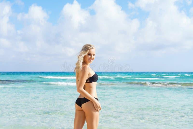 Young woman in a bikini posing on the beach stock photos