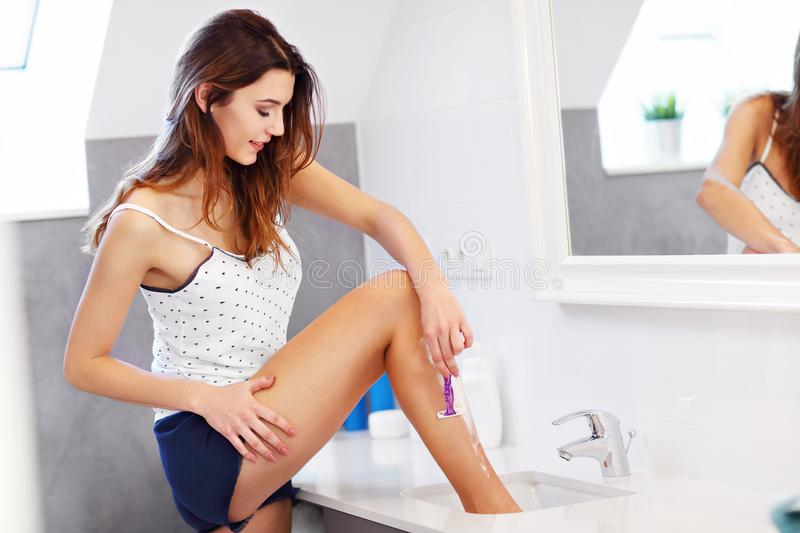 Young woman shaving legs in bathroom in the morning stock photography