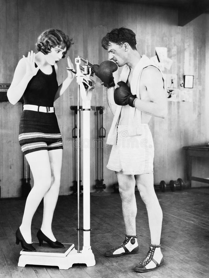 Young woman shocked at her weight with a man in boxing gloves stock photography