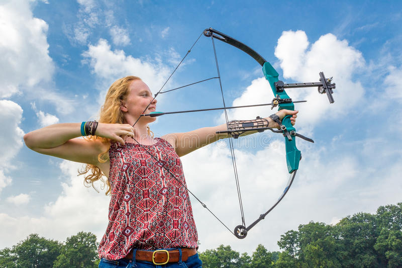 Young woman shooting archery with compound bow and arrow. Young woman shooting archery with compound bow against blue sky and white clouds royalty free stock photos