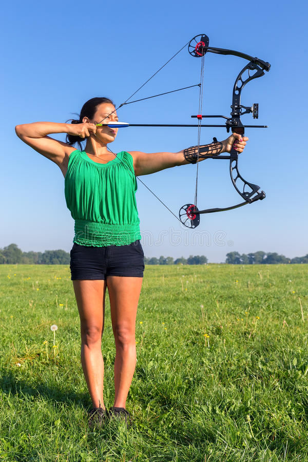 Young woman shooting arrow of compound bow. Young colombian woman shooting arrow of compound bow in meadow stock photos