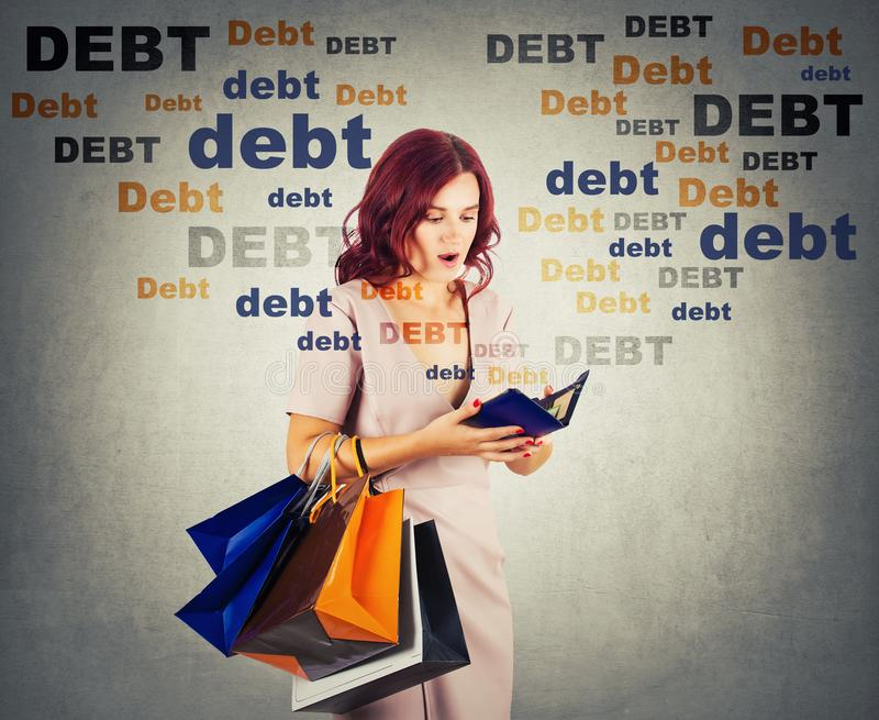 Young woman shopaholic carrying bags holding a empty wallet, shocked about huge debt amount, has no money for shopping in her royalty free stock images
