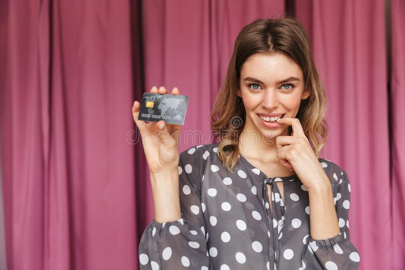 Young woman shopaholic holding credit card. Image of young woman shopaholic standing near changing room indoors looking camera holding credit card royalty free stock photos