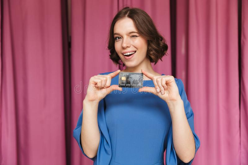 Young woman shopaholic holding credit card. Image of young woman shopaholic standing near changing room indoors looking camera holding credit card royalty free stock image