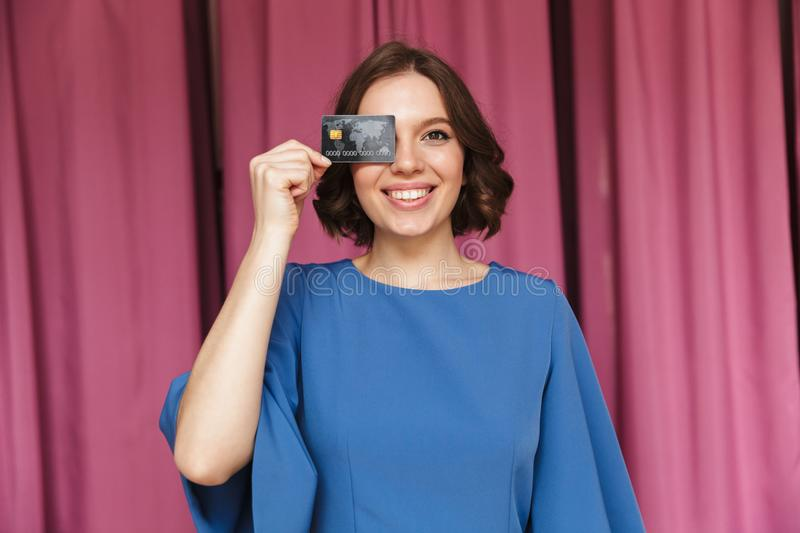 Young woman shopaholic holding credit card. Image of young woman shopaholic standing near changing room indoors looking camera holding credit card royalty free stock images
