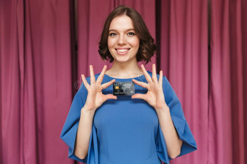 Young woman shopaholic holding credit card. Image of young woman shopaholic standing near changing room indoors looking camera holding credit card stock photo