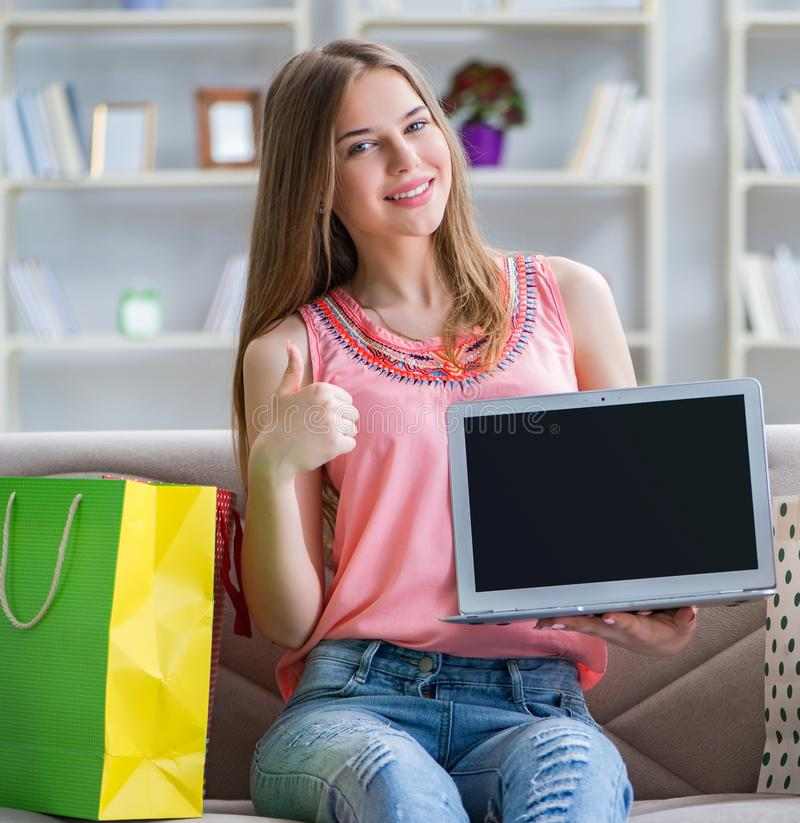 Young woman with shopping bags indoors home on sofa royalty free stock image