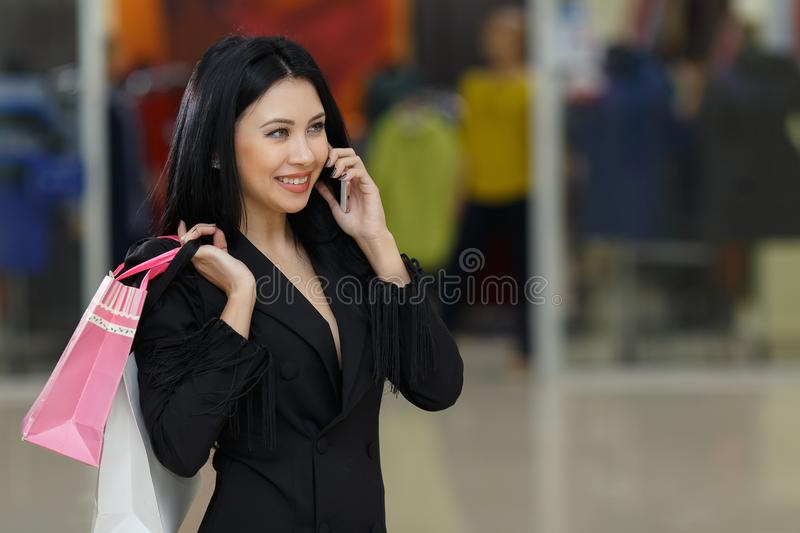 Young woman with shopping bags and talking on mobile phone in the mall. royalty free stock photography