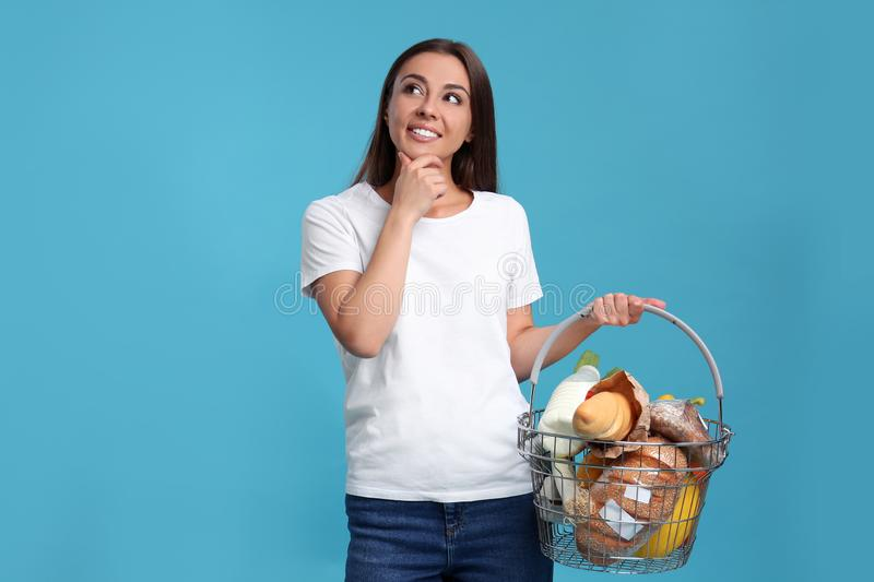 Young woman with shopping basket full of products stock images