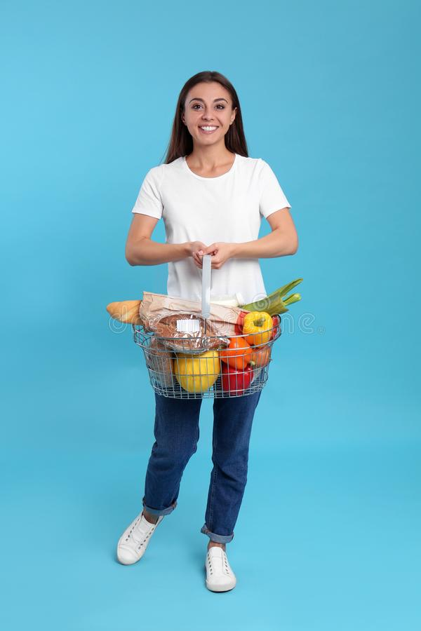 Young woman with  basket full of products on blue background royalty free stock photography
