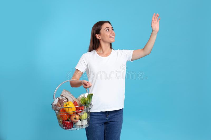 Young woman with  basket full of products on blue background royalty free stock photos