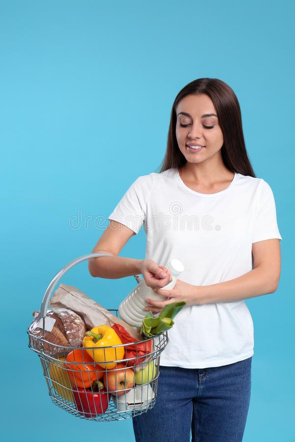 Young woman with  basket full of products on blue background stock photo
