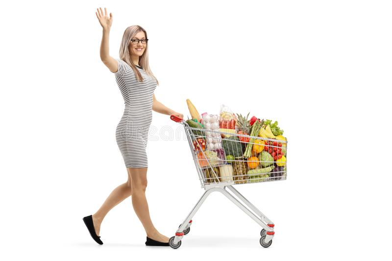 Young woman with a shopping cart full of food products waving royalty free stock photos