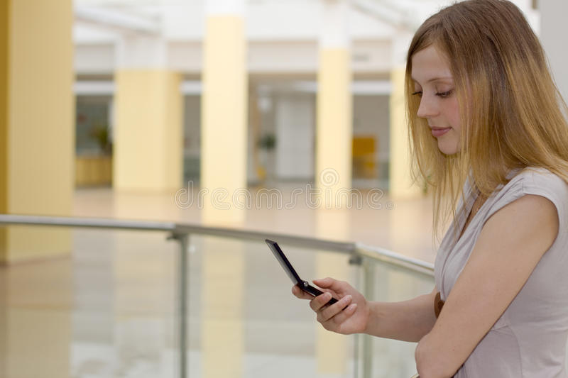 Young woman in shopping centre with cellphone royalty free stock photography