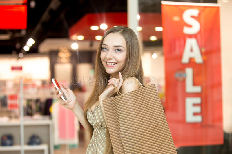 Young woman in a shopping centre holding a phone smiling royalty free stock image