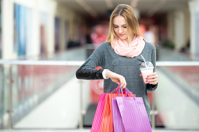 Young woman on shopping looking at her watch royalty free stock photos