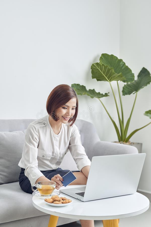 Young woman shopping online with credit card and laptop at home royalty free stock photography