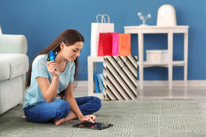 Young woman shopping online with credit card and tablet PC at home stock image