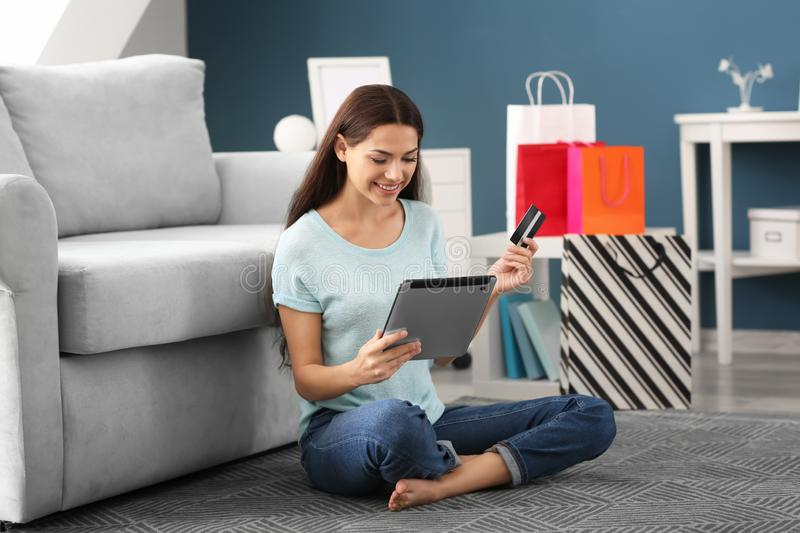 Young woman shopping online with credit card and tablet PC at home royalty free stock photo