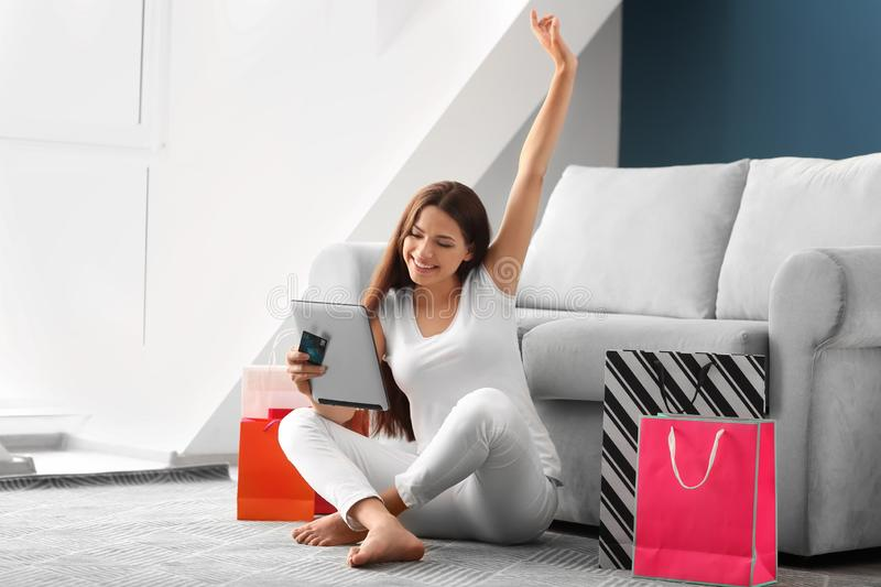 Young woman shopping online with credit card and tablet PC at home stock photography