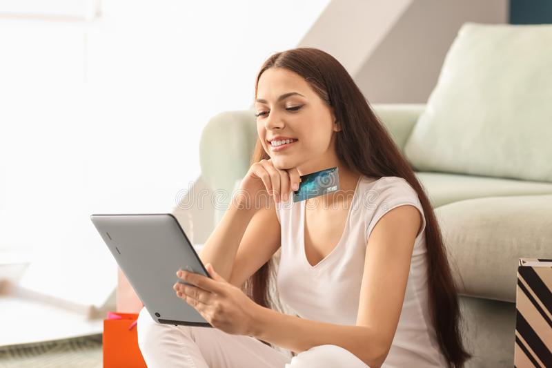 Young woman shopping online with credit card and tablet PC at home royalty free stock image