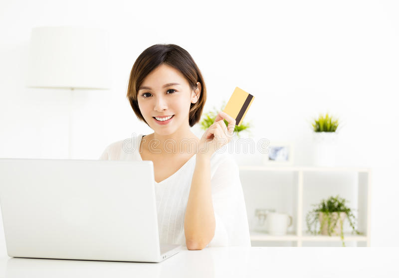 Young woman shopping online and paying with credit card. Young asian woman shopping online and paying with credit card royalty free stock photo