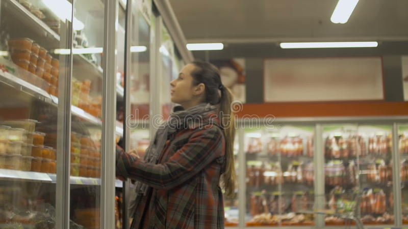 Young woman shopping at supermarket. Opening fridge to pick up refrigerated food stock video footage