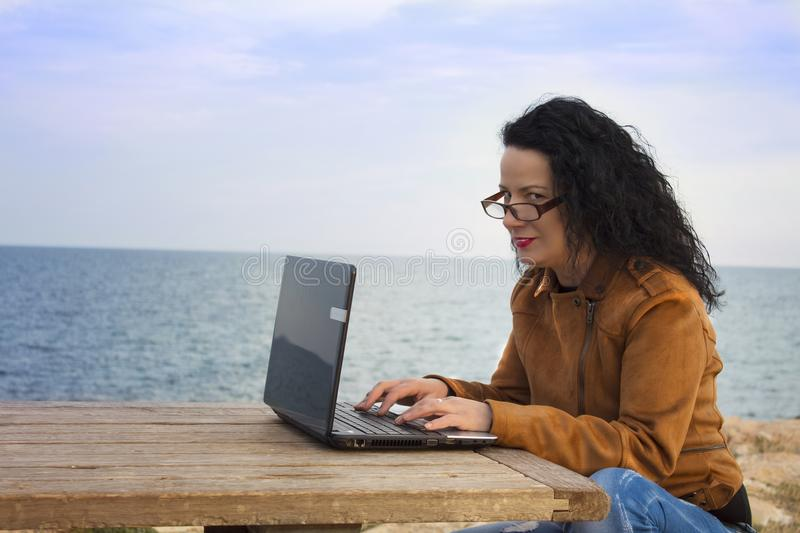 Young woman on shore with computer. stock image