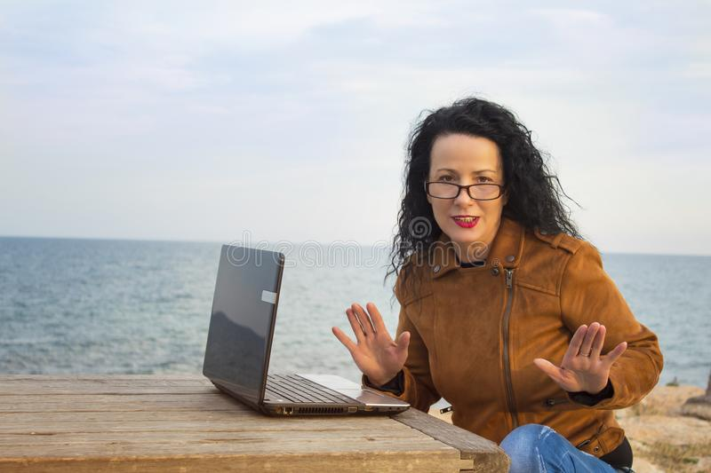 Young woman on shore with computer.4 royalty free stock image