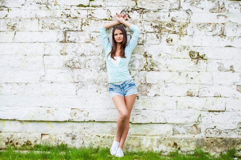 Young woman in short blue jeans shorts posing against a stone wall background royalty free stock image