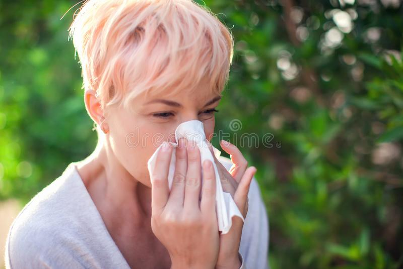 Young woman with short hair sneezing into tissue. flu, allergy, runny nose. Healthcare concept stock photos