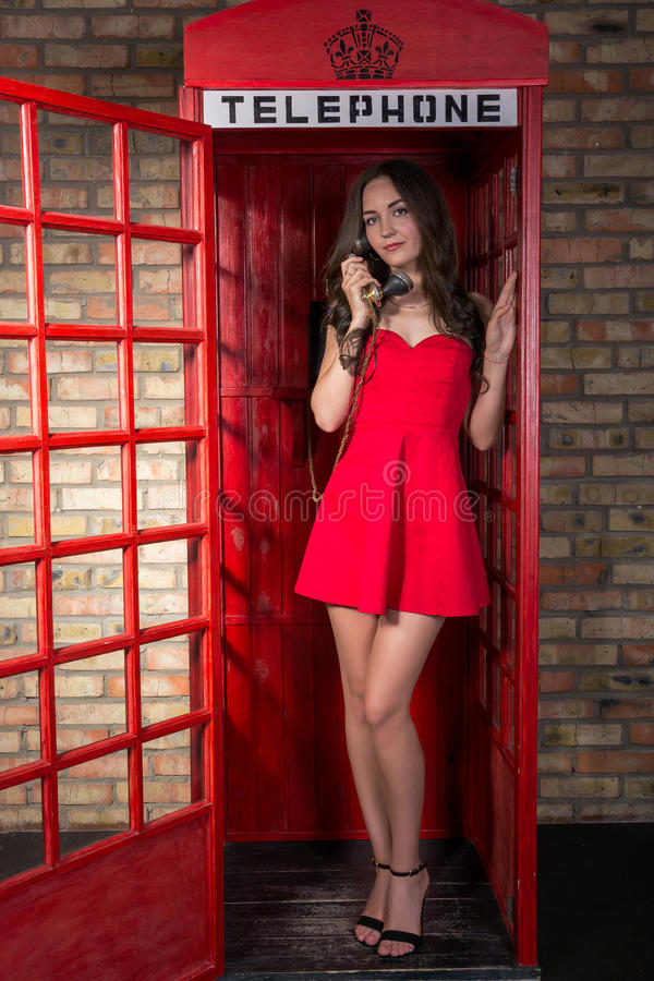 Young woman in a short red dress talking on the phone. In the old phone booth royalty free stock image