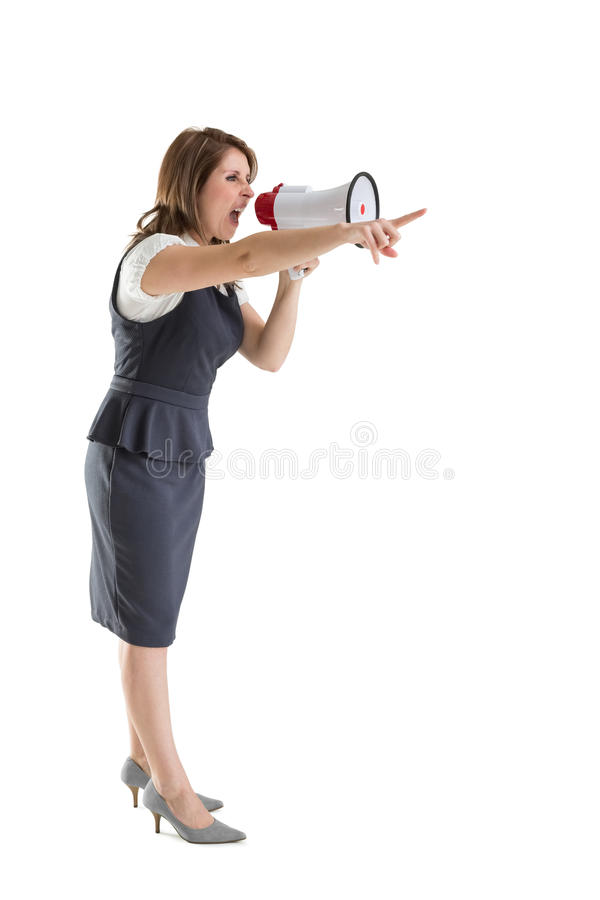 Young woman shouting into bullhorn as she gestures. Young woman shouting into bullhorn as she points over white background royalty free stock image
