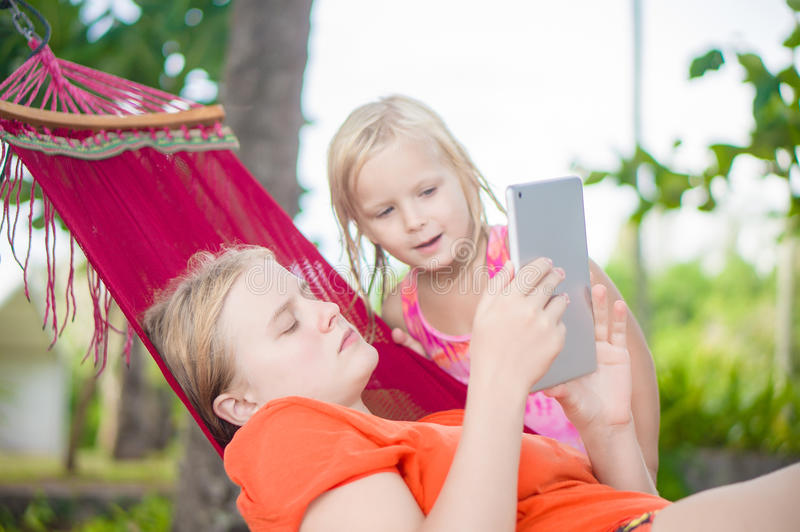 Young woman show pictures to adorable daughter on electronic tab stock image