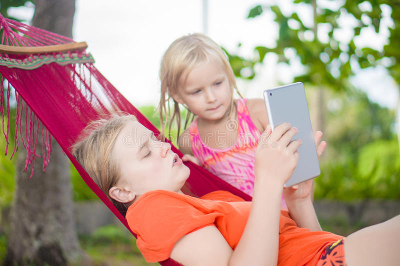 Young woman show pictures to adorable daughter on electronic tab stock photos