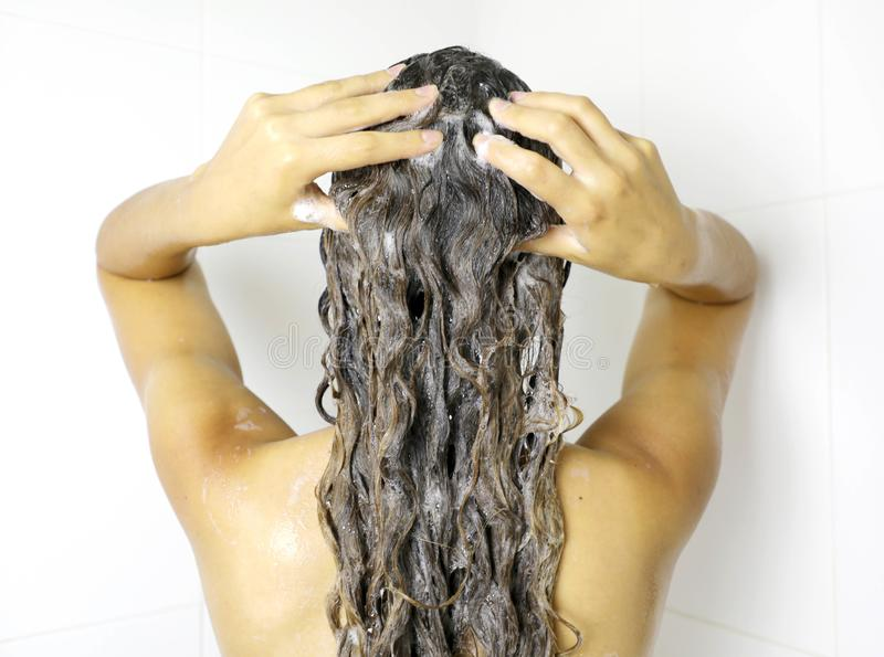 Young woman in shower washing hair with shampoo. Beautiful woman showering washing long hair.  stock photos